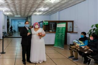 Newlyweds pose for a photo after they were married at the civil registry office