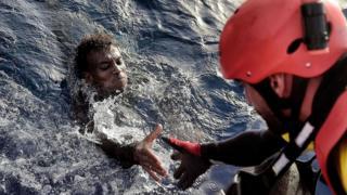 Un inmigrante recibe ayuda de un rescatista