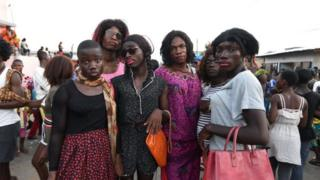 Men from the ethnic southeastern Aboure people, dressed up as women, pose for a photograph during the 38th Edition of the POPO Carnival of Bonoua, 50 kms east of Abidjan, an annual festival held by the Aboure people on April 14, 2018.