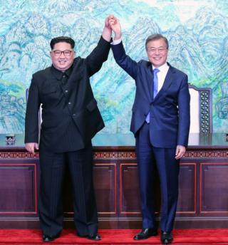 Kim Jong Un and Moon Jae-in hold hands