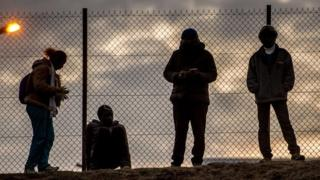 Migrants stand against a chain link fence inside the Eurotunnel site in Coquelles near Calais