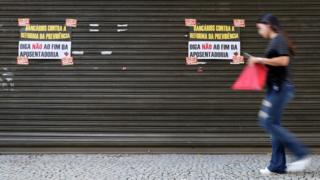 A woman walks past a bank during a general strike against the government's pension plan in Rio de Janeiro