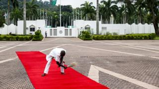 An employee brooms the red carpet ahead of the arrival of German Chancellor Angela Merkel to her meeting with the President of Nigeria at the State House, in Abuja, Nigeria, 31 August 2018.