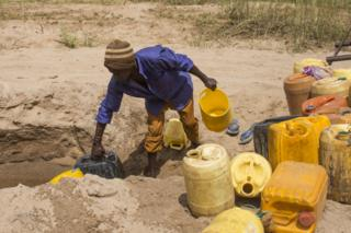 A man collects water on Kikuu River. During the rainy season, water percolates into the sand and is stored underground. Then during the dry season, locals dig small wells in the sand to get water