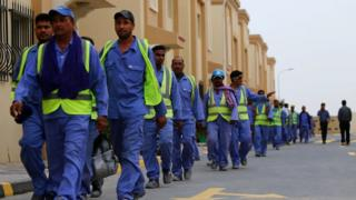 A line of men in high-vis vests walk at a football stadium construction site in Qatar