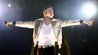 Macklemore, dressed in a white under-vest and metallic gold jacket, stretches his arms out to either side in recognition of the crowd before the NRL grand final in Sydney