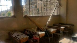 A damaged classroom with dust-covered desks