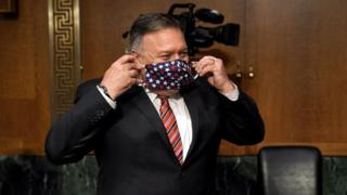 US Secretary of State Mike Pompeo puts on a face mask