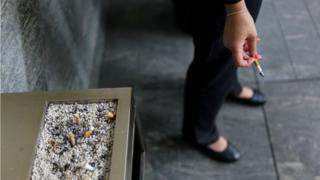건물 앞 담배를 피는 여성