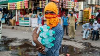 narendra modi A vendor carries bottles of mineral water at a bus depot in Uttar Pradesh.