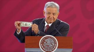 AMLO muestra su billete de dos dólares.