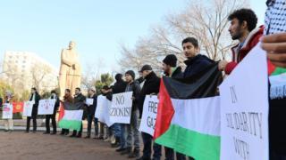 """Активисттер колдоруна """"Мыйзам баарына бирдей болушу керек"""", """"Палестиналыктарга эркиндик"""" деген плакаттарды кармап турушту."""