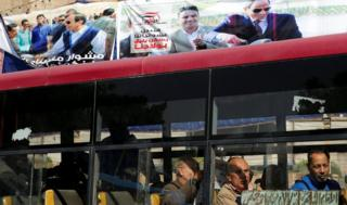 "People look out of a bus window in front of posters of Egypt""s President Abdel Fattah al-Sisi for the upcoming presidential election in Cairo, Egypt February 28, 2018"