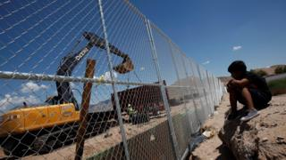 A child looks at U.S. workers building a section of the U.S.-Mexico border wall at Sunland Park, U.S. opposite the Mexican border city of Ciudad Juarez, Mexico, August 26, 2016.