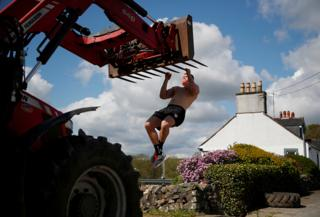 An athlete uses a piece of farm machinery to do pull-ups on