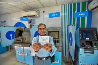 "A man shows a ""no cash"" slip near SBI ATMs in Patna on April 17, 2018. Most of the ATMs have run out of cash in the city"