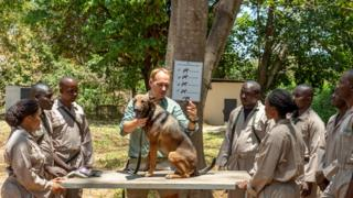 Will Powell, with a dog sitting on a table, talking to trainees during a session in Arusha, Tanzania