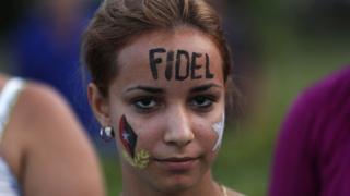 """Una joven cubana con el nombre """"Fidel"""" pintado en su rostro."""