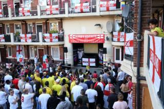 Residents of the Kirby Estate in London watch England play in the World Cup on television