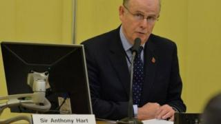 Sir Anthony Hart sits at a desk