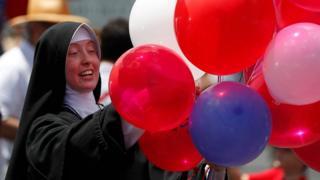 Черниця роздає повітряні кульки кольорів американського прапора на параді у Нью-Йорку.