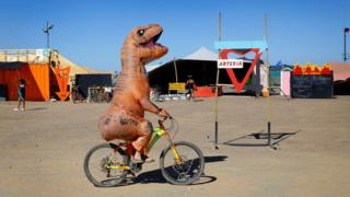 A Burner rides his bicycle wearing a dinosaur costume during the annual Afrikaburn Festival held in the Tankwa Karoo, Calvinia, South Africa