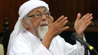 A photograph taken on February 9, 2016 shows that Indonesian cleric Abu Bakar Ba'asyir gestures in jail during a court hearing in Cilacap, Central Java