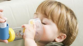 file picture of child with asthma inhaler and spacer device