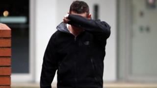 Dean Goble covers his face as he arrives at Swindon Crown Court