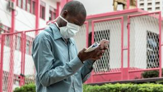 in_pictures A man in a facemask looking at his phone in Yaoundé, Cameroon - Friday 6 March 2020