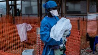 Trabalhador de saúde carrega um bebê de quatro dias, suspeito de ter Ebola, em um Centro de Tratamento de Ebola apoiado por MSF (Médicos Sem Fronteiras) em Butembo, República Democrática do Congo