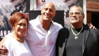 "Rocky Johnson (R) with his son Dwayne ""The Rock"" Johnson (C) and ex-wife Ata Johnson (L)"