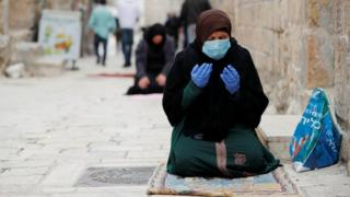A Muslim woman wearing a face mask and rubber gloves prays