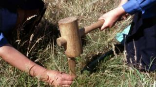 girl guides hammer a tent peg into the ground