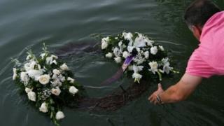 Homem joga coroa de flores na água