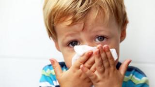 Toddler boy blowing his nose