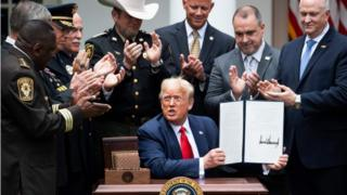 US President Donald Trump shows his signature on an Executive Order on Safe Policing for Safe Communities, in the Rose Garden of the White House
