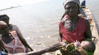 A woman holds a new-born baby, 11 April 2006, aboard a pirogue during a crossing of the Lake Volta