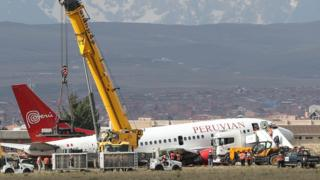 Rescue workers at the El Alto International Airport in Bolivia try to tow a stranded plane, 22 November 2018.