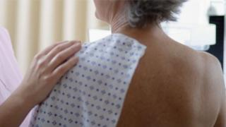 A woman in hospital gown