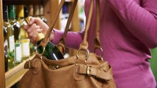Woman stealing bottle of wine from shop