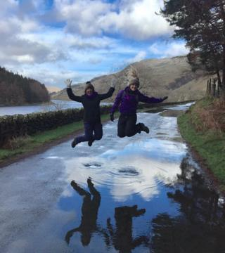 Two people jumping over a puddle of water