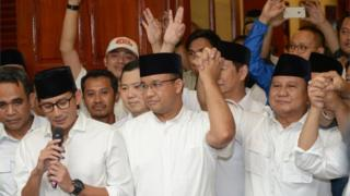 Jakarta governor-elect Anis Baswedan (C), his deputy governor-elect Sandiaga Una (L) and Prabowo Subianto (R) of the Gerindra party hold hands together during a press conference in Jakarta on April 19, 2017