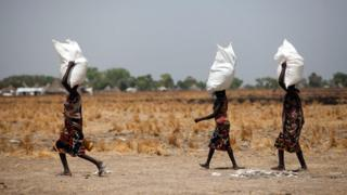"""Three women carry a sack of food distributed on March 4, 2017, in Ganyiel, Panyijiar county, in South Sudan. South Sudan was declared the site of the world""""s first famine in six years, affecting about 100,000 people."""
