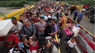 Venezuelanos cruzando a fronteira da Venezuela com a Colômbia