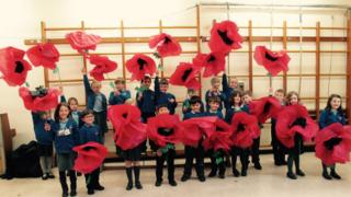 Children from Rhos St Primary School with poppies