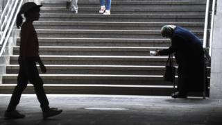 Женщина просит милостыню в переходе
