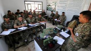 جنود بالحشد الشعبي يستمعون، في معسكر بالبصرة، إلى شرح من مدربهم على التعامل مع المتفجرات.