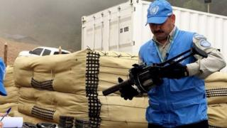 United Nations Mission in Colombia shows one of its members carrying FARC weapons during an inspection at La Elvira, Colombia, 13 June 2017.