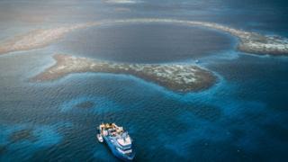 Vista aérea do Buraco Azul de Belize - um círculo azul escuro no meio do mar, cercado por recifes